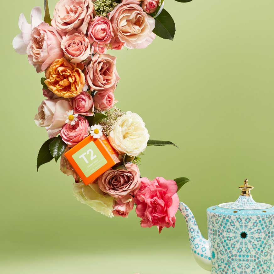 A bouquet of roses with a box of T2 Green Rose Tea inside